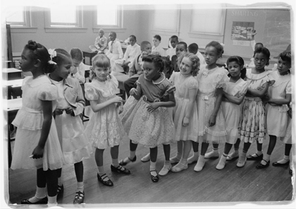 Photograph shows a line of African American and white school girls standing in a classroom while boys sit behind them.
