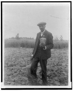 [George Washington Carver, full-length portrait, standing in field, probably at Tuskegee, holding piece of soil]. Photo by Frances B. Johnston, 1906. //hdl.loc.gov/loc.pnp/cph.3c14302