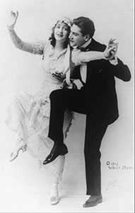 Man in tuxedo and woman in wedding gown dancing.