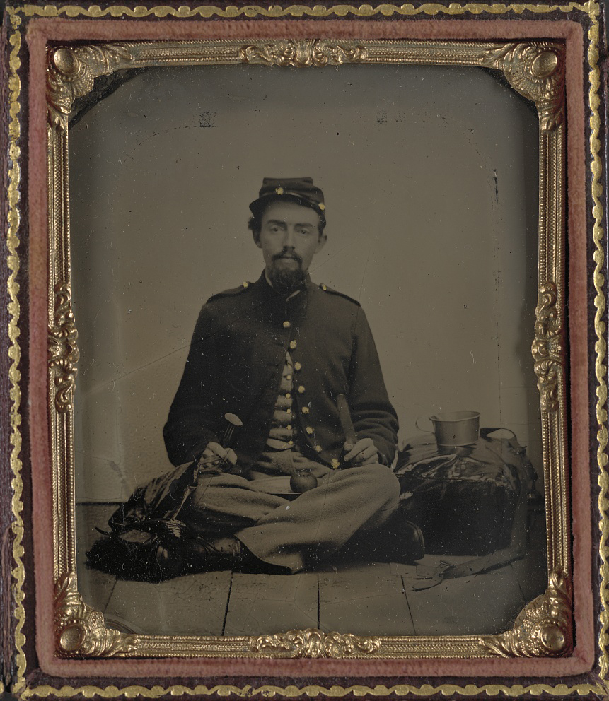 [Unidentified soldier in Union uniform with fork, knife, plate, and cup sitting on the floor and preparing to eat a slice of the apple on his lap]. Tintype, between 1861 and 1865. //hdl.loc.gov/loc.pnp/ppmsca.32132