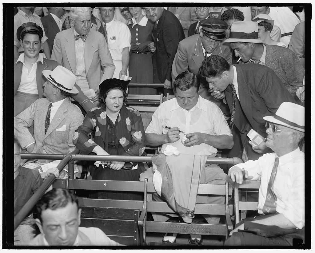 "The Bam still a favorite. Washington D.C. July 7. Although out of baseball for the last few years, ""Babe"" Ruth still retains his popularity with the millions of baseball fans the country over. With Mrs. Ruth the ""Babe"" is shown autographing a ball for an admirer at the All-Star game today at Griffith Stadium. Photo by Harris & Ewing, 1937 July 7. //hdl.loc.gov/loc.pnp/hec.22986"