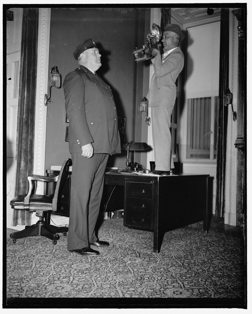 Initiative needed here. Washington, D.C., June 3. Initiative was certainly needed when Clarence Jackson, diminutive news photographer, was sent to get a closeup of policeman Edward F. Brown, 6 foot, 9 1/2 inch arm of the law who guards the entrance to the Senate cloakroom at the Capitol. Jackson got the picture even though he had to resort to a desk to get on speaking terms with the huge policeman. Photo by Harris & Ewing, 1938. //hdl.loc.gov/loc.pnp/hec.24695