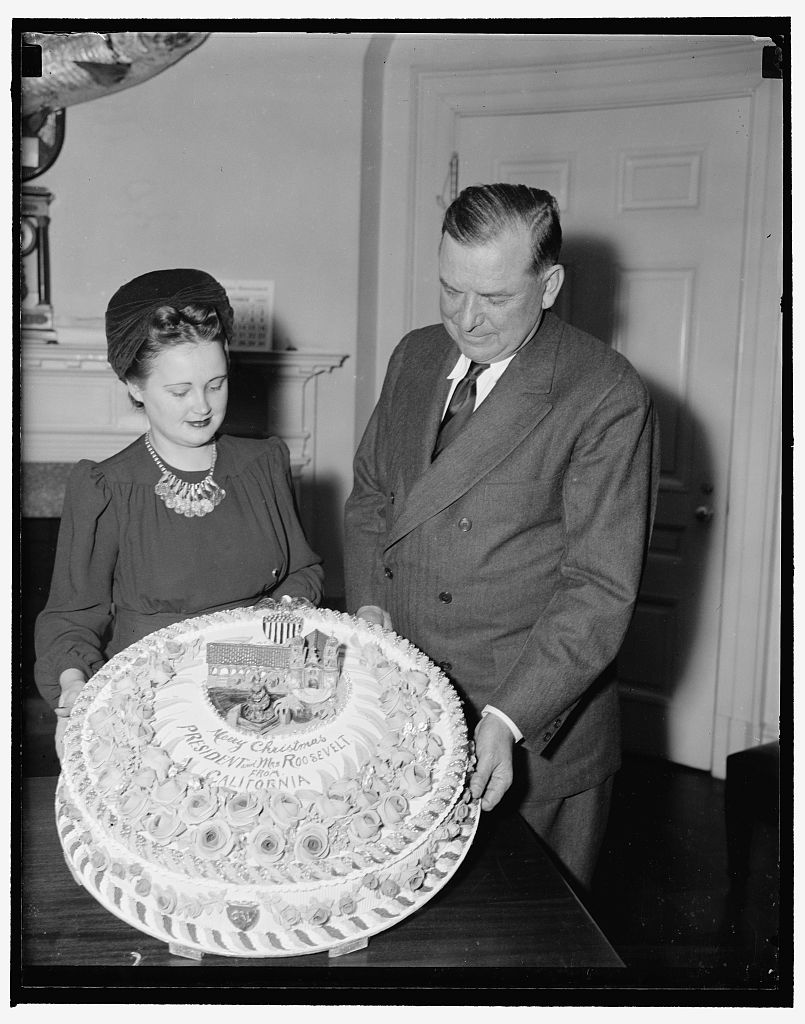 President gets Xmas fruit cake. Washington, D.C., Dec. 19. Brig. Gen. Edwin Watson, a Presidential Secretary, accepting for President Roosevelt a fruit cake from Miss Mildred Cook, Secretary to Rep. A.J. Elliott of California. The cake is a gift from W.C. Baker of Ojai, Calif., who has baked cakes for the White House for the last 17 years. Photo by Harris & Ewing, 1939. //hdl.loc.gov/loc.pnp/hec.27837