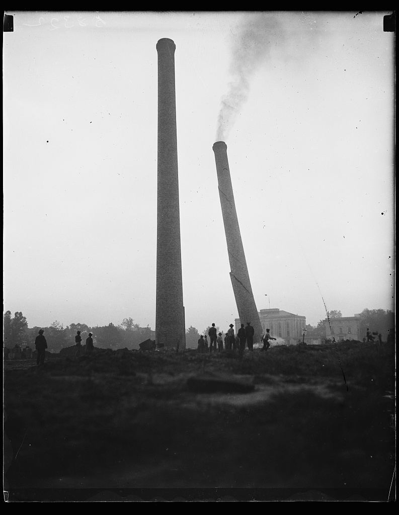Don't want smokestacks, Wash. D.C. These two 150-foot tall brick smokestacks on the mall in Washington, D.C. were considered an eye sore and ordered demolished. This picture shows one toppling. The other fell shortly thereafter. They first were erected when a central heating plant occupied the site. Photo by Harris & Ewing, 1935 September 17. //hdl.loc.gov/loc.pnp/hec.39414
