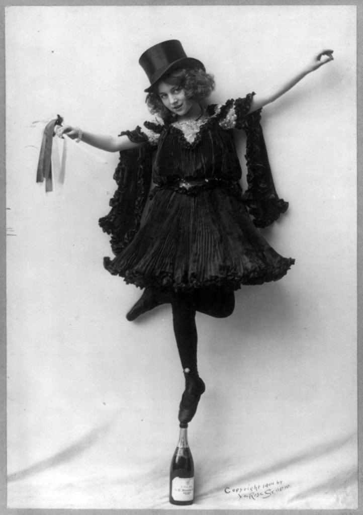 Model posed wearing black pressed pleats, top hat, and ballet shoes, standing tip-toe on champagne bottle. Photo copyrighted by Ye Rose Studio, 1904. //hdl.loc.gov/loc.pnp/cph.3b03473