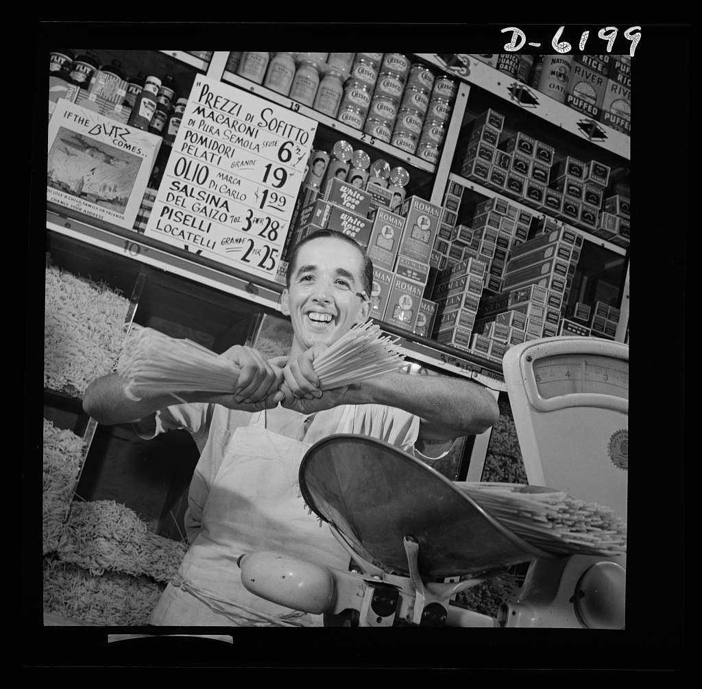 Posting ceiling prices in foreign languages. Charles Ruggiero, clerk in a grocery store in New York's Italian section, wishes the handful of spaghetti he is breaking were Mussolini's neck. The ceiling price sign above his head, written in Italian, is helping to defeat Il Duce by controlling inflation, one of America's most dangerous enemies. Photo by Howard Liberman, July 1942. //hdl.loc.gov/loc.pnp/fsa.8b07443