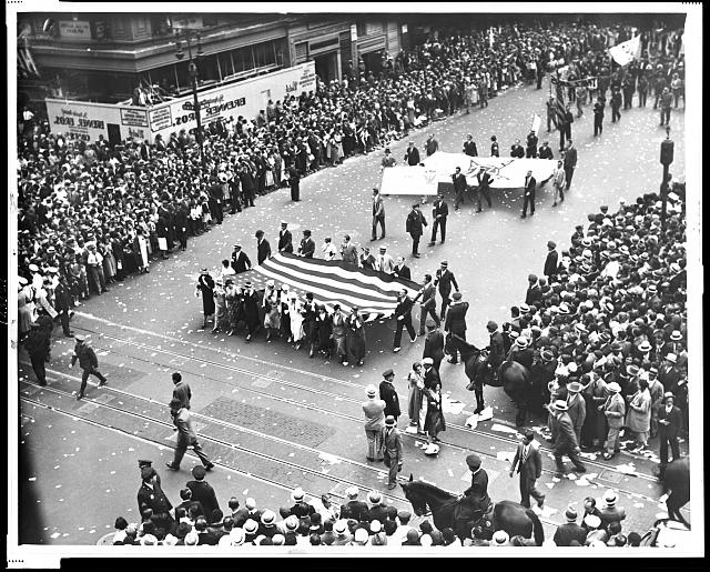 Female film industry workers carrying a large American flag as part of an National Recovery Administration parade, New York City. Photo by World-Telegram staff photographer, 1933.//hdl.loc.gov/loc.pnp/cph.3c23321
