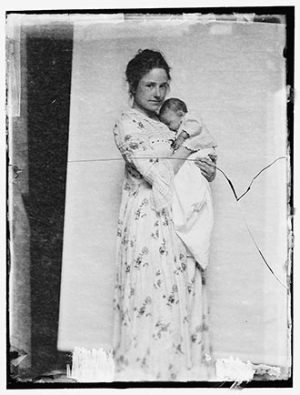 Gertrude Kasebier's daughter, Gertrude Kasebier O'Malley, full-length portrait, standing, facing front, holding her infant son Charles O'Malley.