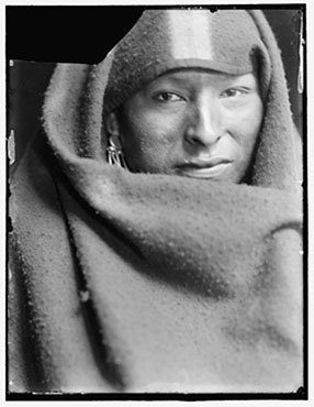 American Indian man, probably a member of Buffalo Bill's Wild West Show, bust portrait, facing front, wrapped in blanket.