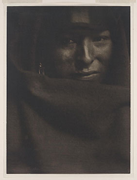 Photograph shows head-and-shoulders portrait of Native American man.