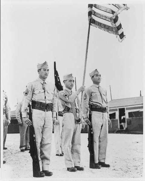 Two Masaoka brothers ... flank flag bearer at Camp Shelby, Mississippi. Photo by U.S. Army Signal Corps, 1944 April. //hdl.loc.gov/loc.pnp/cph.3c11187