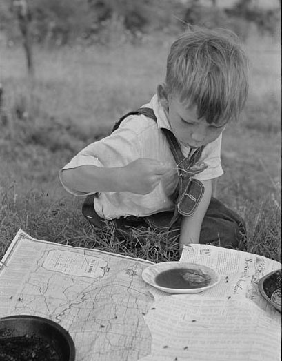 Son of white migrant eating lunch of blackberry pie along the highway east of Fort Gibson, Oklahoma. Photo by Russell Lee, 1939. //hdl.loc.gov/loc.pnp/fsa.8a26524