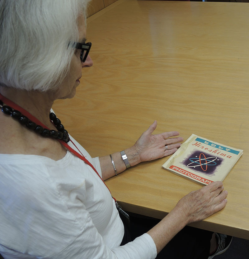 Verna Curtis looking at Hiroshima: Photograph, published by the Hiroshima Peace Committee. Photo by Kristi Finefield, 2015.