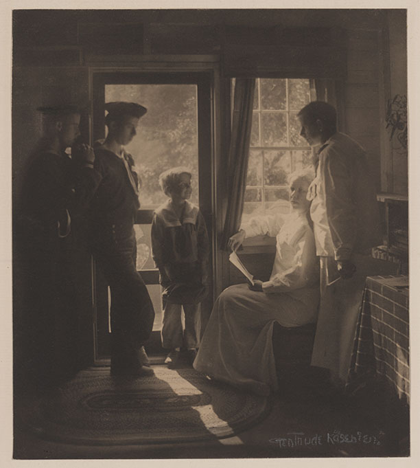 Photo shows Clarence White and family, posed just inside doorway, at F. Holland Day's house in Maine.