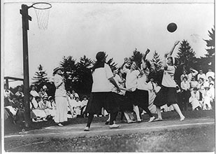 Photograph shows women of Vassar College playing outdoor game of basketball with a few spectators in attendance.