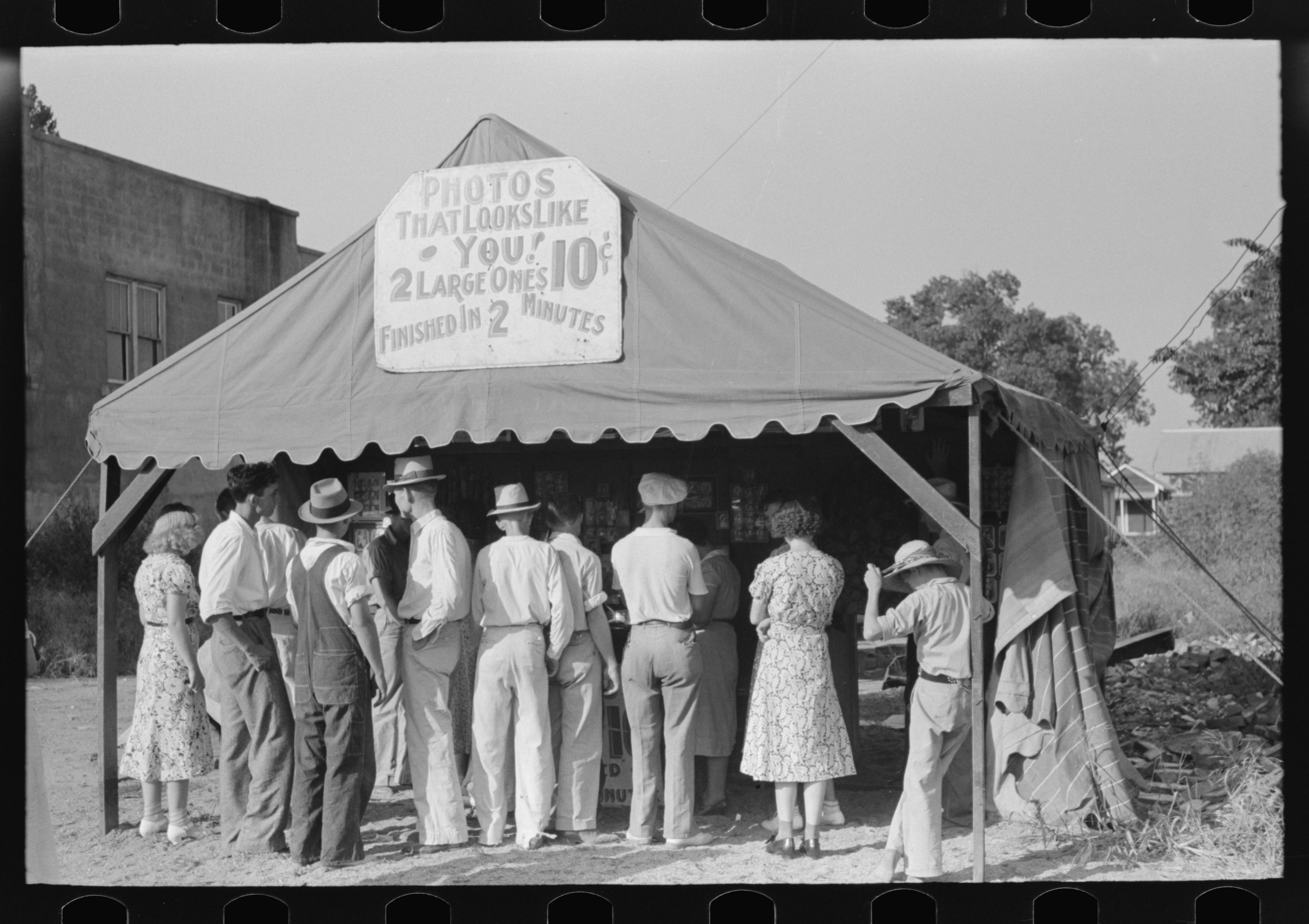 Steele, Missouri. A crowd in front of an itinerant photographer's tent. Photo by Russell Lee, 1938 Aug. hdl.loc.gov/loc.pnp/fsa.8a23444