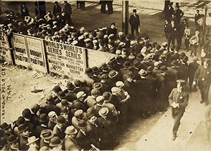 Photograph shows lines of baseball fans along a fence outside the Polo Grounds in New York for a World Series game in 1911 or 1912.