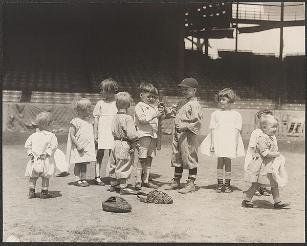 Young boys and girls on the baseball field at a major league stadium.