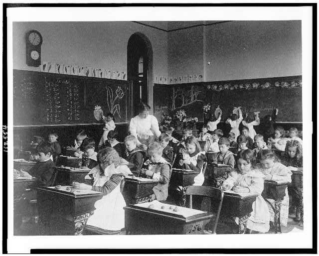 Children modeling clay at desks and drawing on blackboard in Washington, D.C. classroom. Photo by Frances Benjamin Johnston, 1899? //hdl.loc.gov/loc.pnp/cph.3c12554