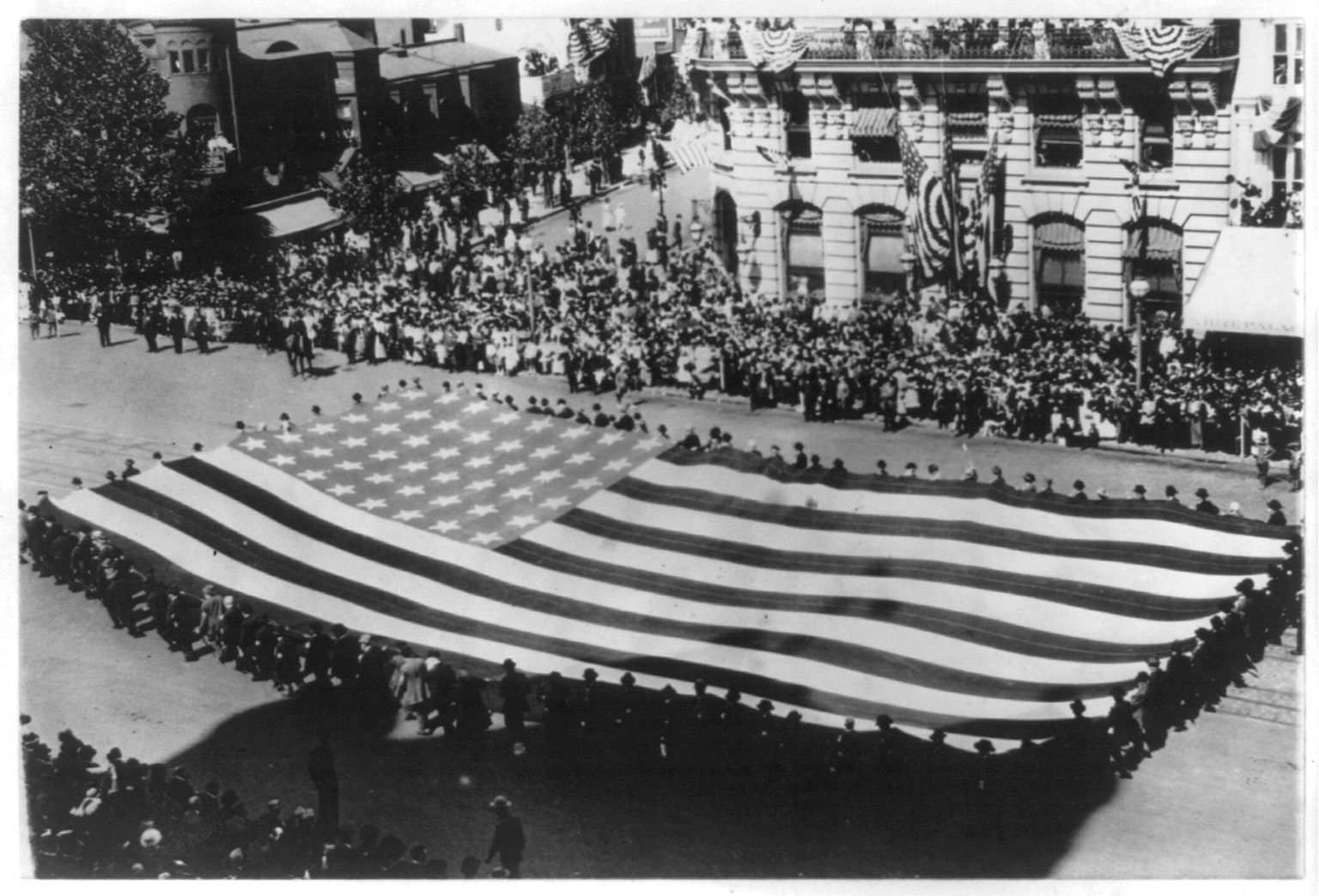 [Huge flag being carried by a large group of men in a G.A.R. parade in Washington, D.C.] Photo by National Photo Company, 1915. //hdl.loc.gov/loc.pnp/cph.3b17255