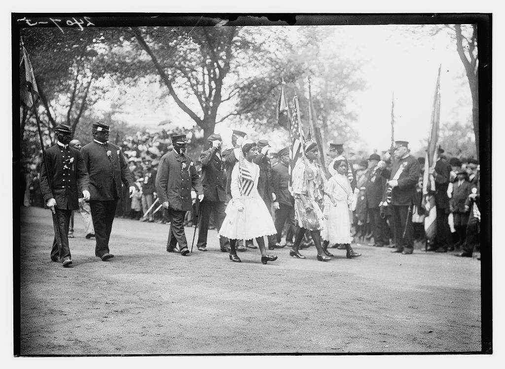 May 30 '12, N.Y. [African American Civil War veterans wearing G.A.R. caps and uniforms and young women marching in procession.] Photo by Bain News Service, 1912 May 30. //hdl.loc.gov/loc.pnp/ggbain.50141