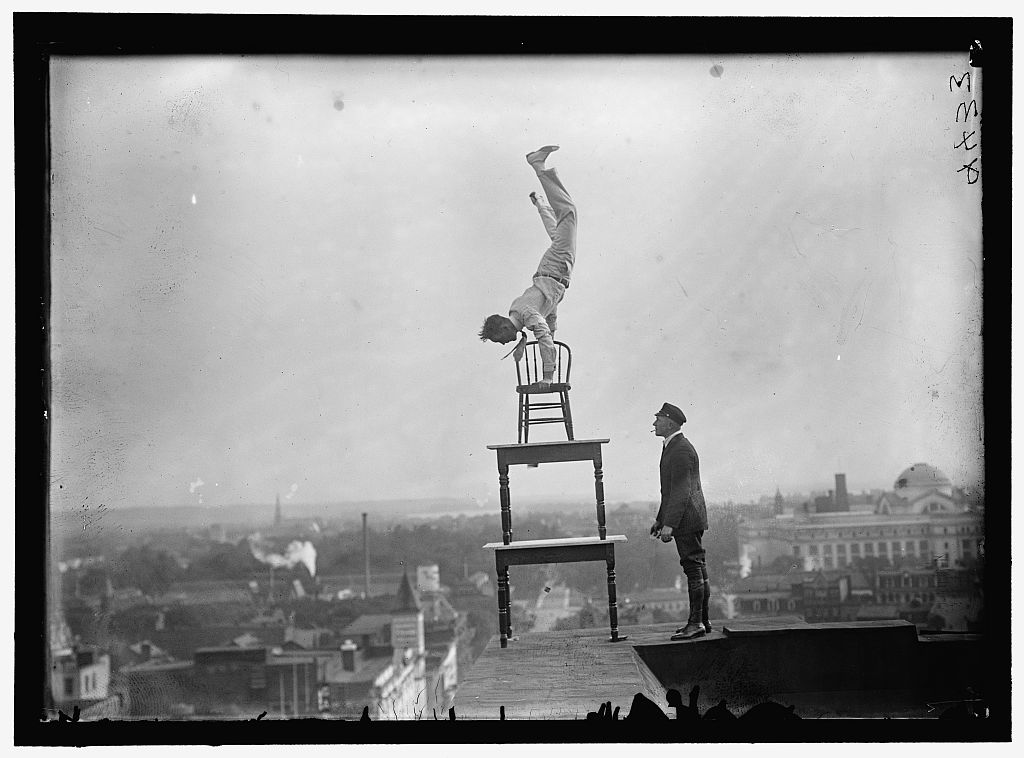 REYNOLDS, J., PERFORMING ACROBATIC AND BALANCING ACTS ON HIGH CORNICE ABOVE 9TH STREET, N.W. Photo by Harris & Ewing, 1917. //hdl.loc.gov/loc.pnp/hec.09580