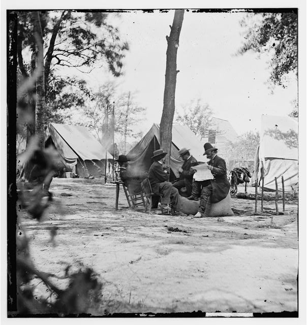 Gen. Ambrose E. Burnside (reading newspaper) with Mathew B. Brady (nearest tree) at Army of the Potomac headquarters. Photograph (left half of stereo negative), 1864 June 11 or 12. //hdl.loc.gov/loc.pnp/cwpb.01703