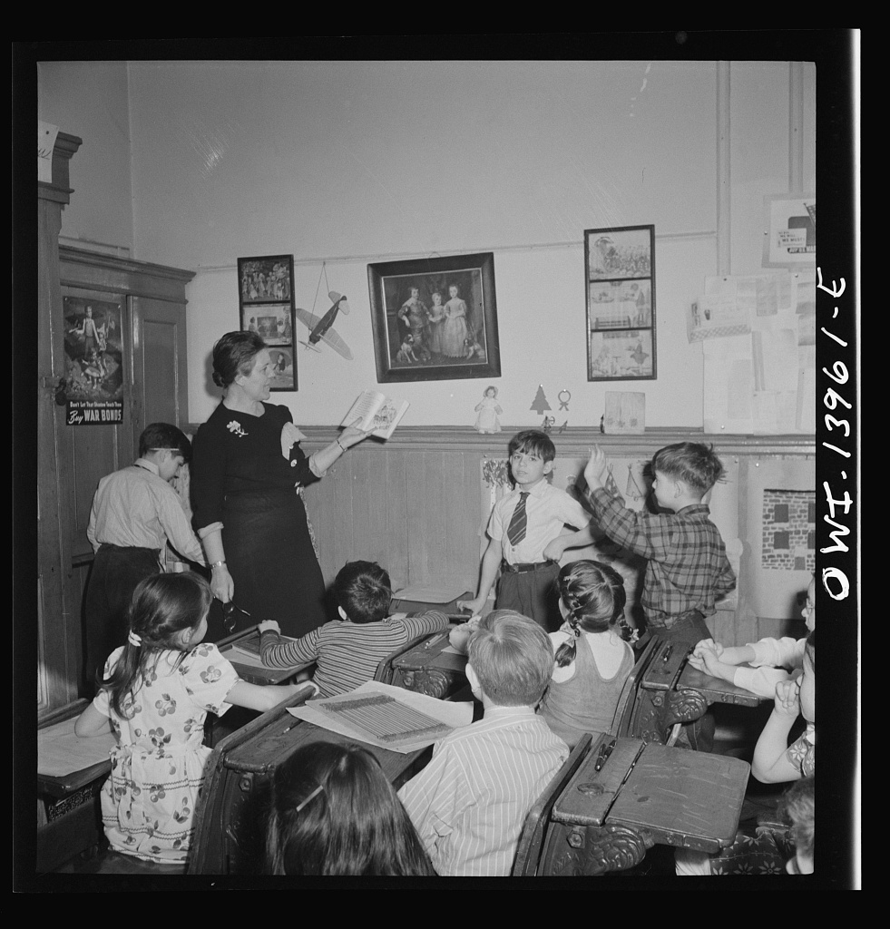 "New York, New York. Class in Public School Eight on King Street, discussing a book entitled ""We love America,"" brought to school by one of the pupils. Photo by Marjory Collins, 1943 Jan. //hdl.loc.gov/loc.pnp/fsa.8d24386"