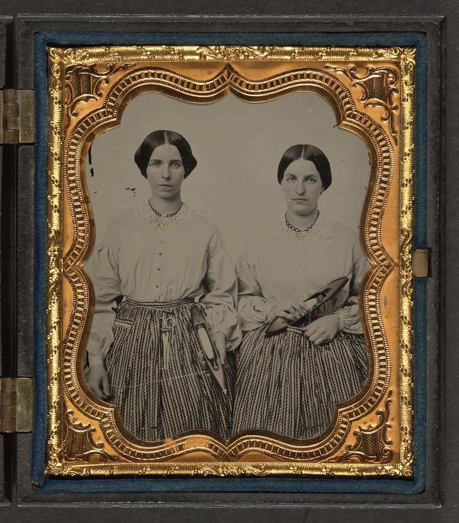 [Sisters Lucretia Electa and Louisa Ellen Crossett in identical skirts, blouses, and jewelry with weaving shuttles] Ambrotype by Alfred Hall, 1859 September 26. //hdl.loc.gov/loc.pnp/ppmsca.36964