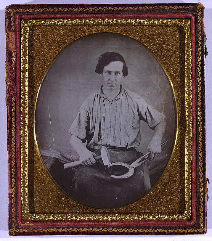 [Occupational portrait of a blacksmith, three-quarter length, facing front, holding a horseshoe with pliers in one hand, and a hammer in the other] Daguerreotype, between 1850 and 1860. //hdl.loc.gov/loc.pnp/cph.3g03948