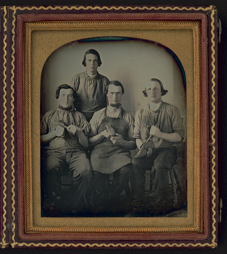 [Occupational group portrait of four shoemakers, one full-length, standing, other three seated, holding shoes and shoe making equipment] Daguerreotype, between 1840 and 1860. //hdl.loc.gov/loc.pnp/ppmsca.51946