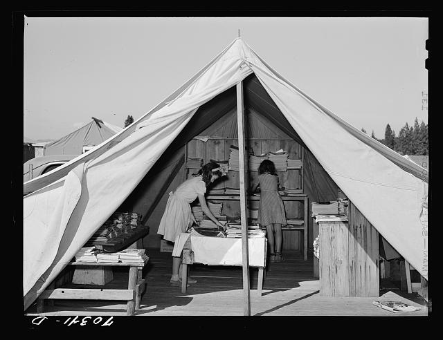 Library tent at the FSA (Farm Security Administration) mobile camp for migratory farm workers. Odell, Oregon. The girls working in the library receive credit in the Junior Campers League for work in the library . Photo by Russell Lee, 1941 Sept. //hdl.loc.gov/loc.pnp/fsa.8c22565