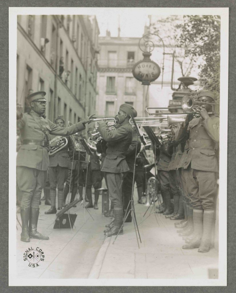 Genuine jazz for the yankee wounded In the courtyard of a Paris hospital for the American wounded, an American negro military band, led by Lt. James R. Europe, entertains the patients with real American jazz. Photograph by United States Army Signal Corps, 1918. //hdl.loc.gov/loc.pnp/ds.09800