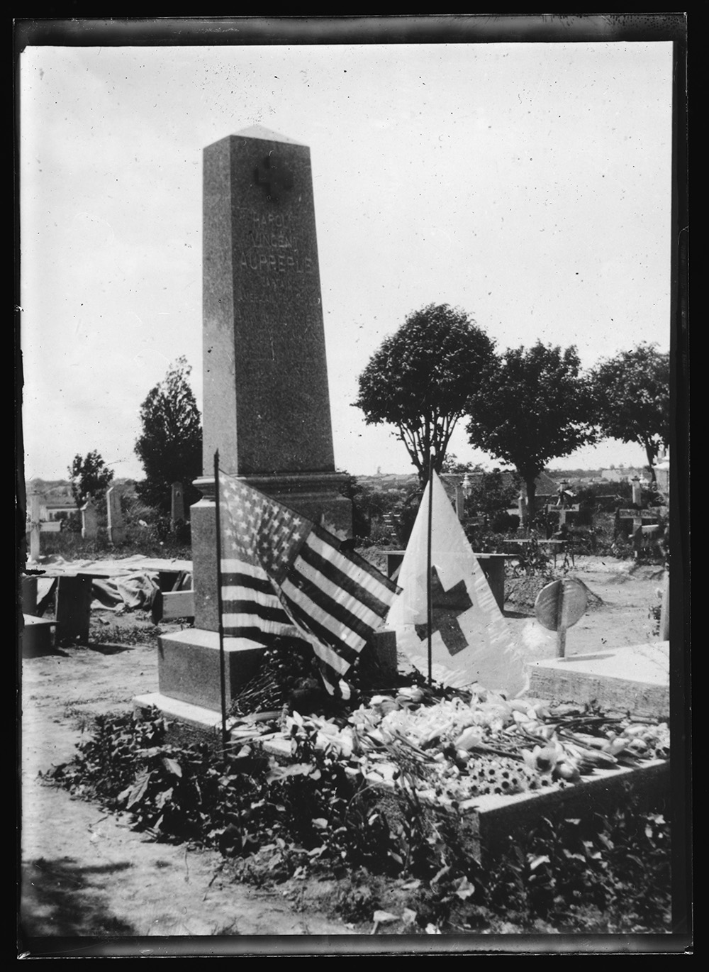In far off Serbia. Graves of Americans who died while carrying on relief work of America were not forgotten on Decoration Day even in far away Serbia. This picture shows the grave of Capt. Harold V. Aupperle of the American Red Cross, formerly of Junction City, Colorado, who died at Nova Varosh, Serbia on June 14, 1919, while engaged in relieving the suffering of that country. Red Cross workers and Serbians united in placing flowers and flags upon the grave. Photo, American National Red Cross photograph collection, 28 August 1920 [date received]. //hdl.loc.gov/loc.pnp/anrc.11898