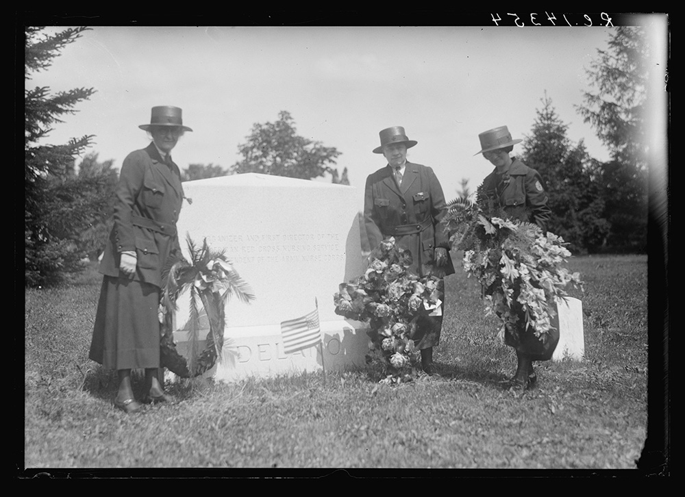 Graves, U.S. NURSES HONOR JANE A. DELANO. Tributes to the memory of Jane A. Delano, head of the Nursing Service of the American Red Cross who died on duty in France in 1919, were laid on Memorial Day on the spot where she sleeps in Arlington. Miss Clara D. Noyes, National Director of the Red Cross Nursing Service (on left), with the wreath from the American Red Cross; Miss Ida Butler, Assistant National Director (on right), with the wreath from the Alumnae of the University of Pennsylvania Hospital, of which Miss Delano had been Superintendent of Nurses, and Mrs. Annie Humphrey (centre), Director of Home Hygiene and Care of the Sick, Washington Division, Charter member of the Jane A. Delano Post No. 344 Nurses of the American Legion, New York, with the wreath from that Post. Photo, American National Red Cross Photograph Collection, 1924. //hdl.loc.gov/loc.pnp/anrc.15198