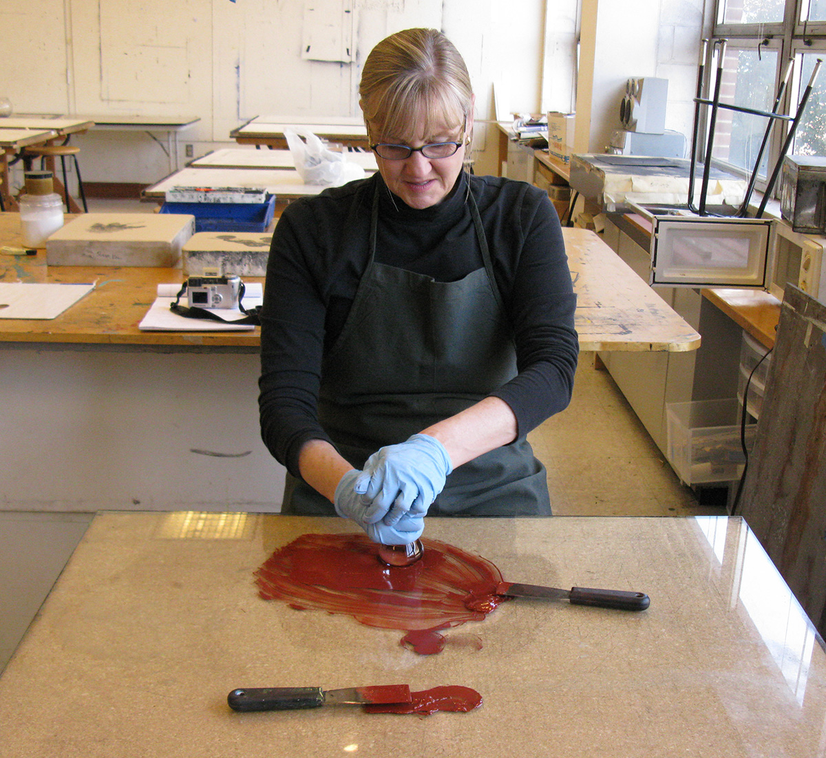 Linda Stiber Morenus using a glass muller to hand-mix dry red-ochre pigment into linseed oil; making ink based on historical recipes to print Renaissance-style chiaroscuro woodcut recreations. Photo by Katherine Blood, 2018.