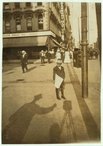 John Howell, an Indianapolis newsboy ... Photo by Lewis Hine, 1908 Aug. (The shadow of the photographer and his camera are in the foreground.) National Child Labor Committee Collection //hdl.loc.gov/loc.pnp/nclc.03225