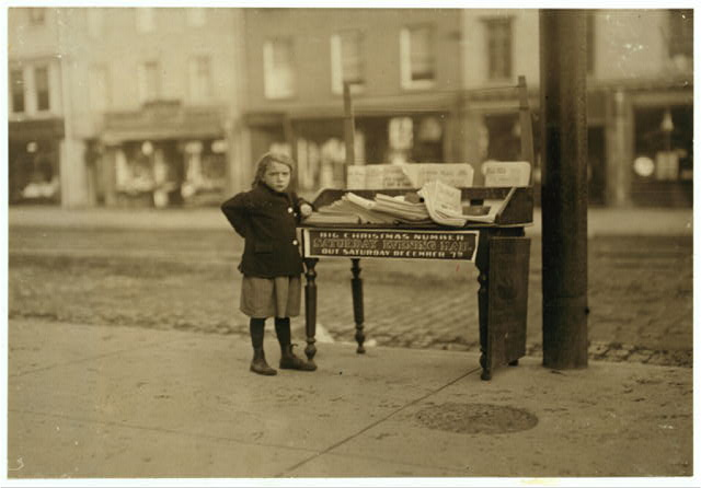 Little girl, apparently 6 yrs. old - but didn't know her name or age - tending stand at Washington and 3rd St. for older sister...Hoboken, New Jersey. Photo by Lewis Hine, 1912 December. National Child Labor Committee Collection. //hdl.loc.gov/loc.pnp/nclc.03824