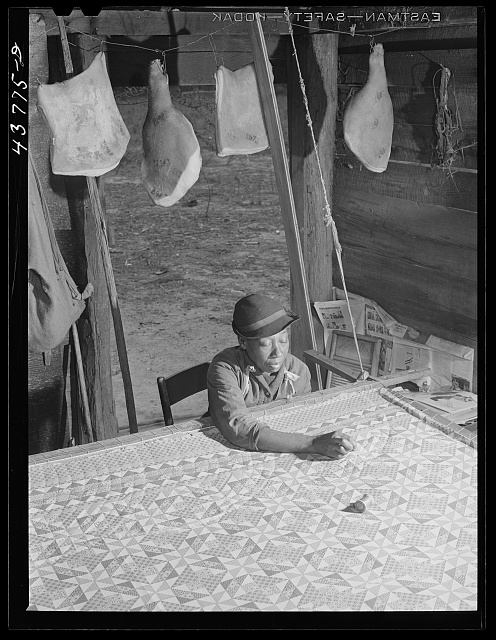 Woman who has not yet found a place to move out of the Hinesville Army camp area working on a quilt in her smokehouse. Near Hinesville, Georgia. Photo by Jack Delano, 1941 April. //hdl.loc.gov/loc.pnp/fsa.8c05198
