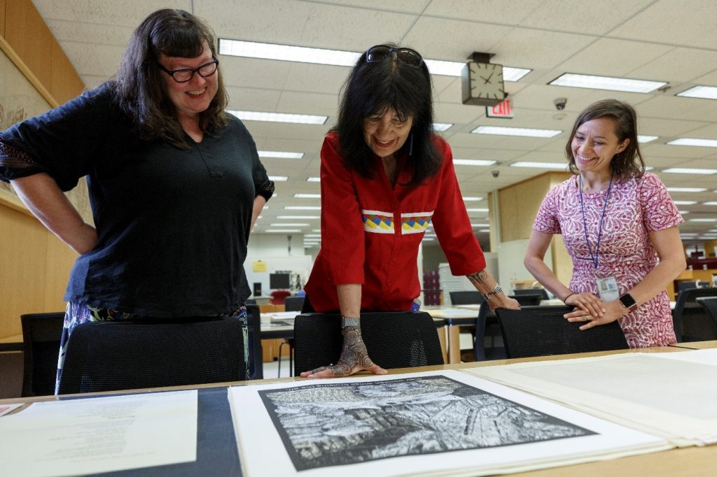 Katherine Blood, Joy Harjo and Melissa Lindberg – looking at a woodcut print by Alice Leora Briggs responding to Mark Strand's poem The Room. Photo by Shawn Miller, 2019.