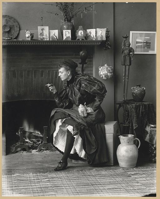 Frances Benjamin Johnston, full-length portrait, seated in front of fireplace. Photo (gelatin silver print) by Frances Benjamin Johnston, 1896. //hdl.loc.gov/loc.pnp/ppmsca.38981