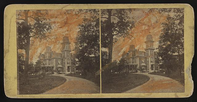 Path leading to large multi-story structure, some discoloration apparent on the photo and some breakage on the stereograph mount