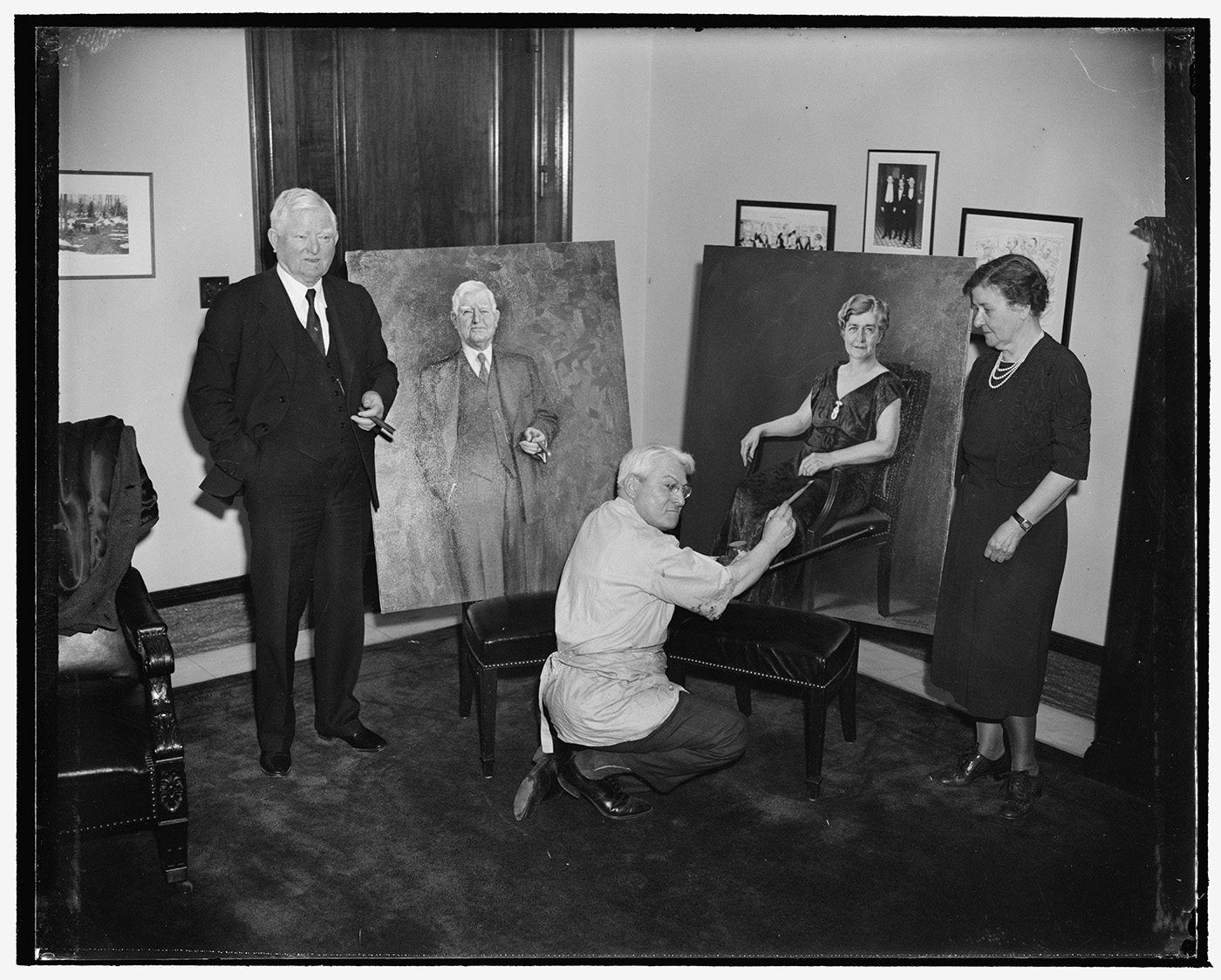 Vice President and Mrs. Garner pose for portraits. Washington, D.C., April 20. Seymour M. Stone, American artist, puts the finishing touches on the portraits of Vice President and Mrs. John N. Garner which he has recently completed. Artist Stone painted the two portraits in two weeks.