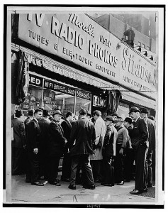 Crowd listens outside radio shop