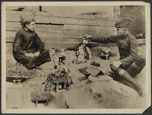 A small French boy sitting next to his plan for a trench sector, constructed in miniature form. A U.S. soldier is touching an American flag sticking out of miniature sandbags.