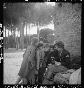 Toni Frissell, sitting, holding camera on her lap, with several children standing around her, somewhere in Europe, 1945
