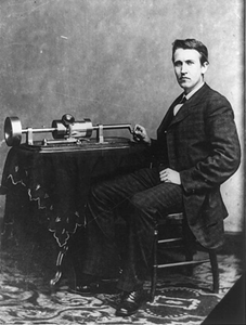 Thomas Edison, full-length portrait, seated, facing front, with phonograph, Library of Congress
