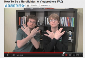 "Screenshot of the VlogBrothers, Hank and John Green, as they display a symbol of their channel in a video titled ""How To Be a Nerdfighter: A Vlogbrothers FAQ"""
