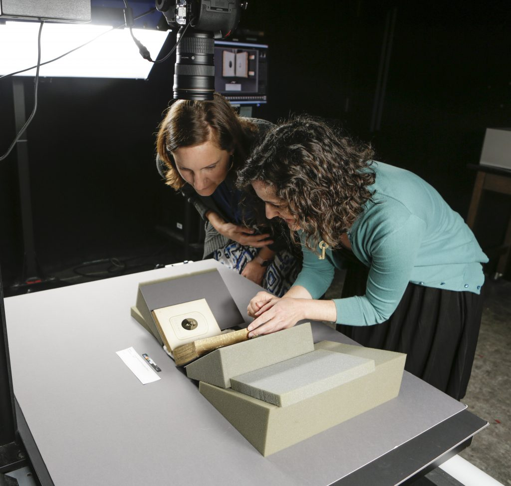 Two conservators stand over a table tophotograph an early photograph of Harriet Tubman
