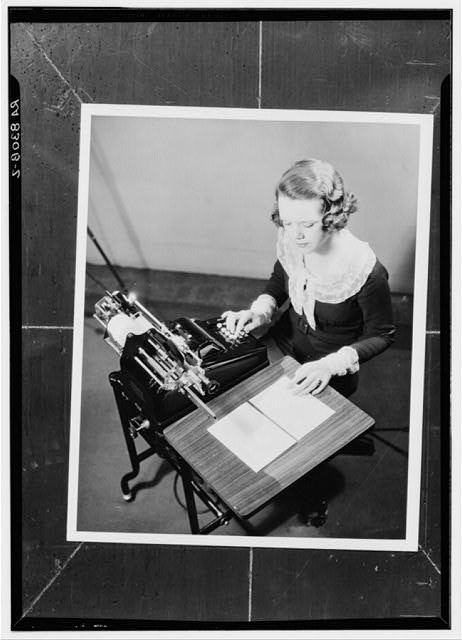 Photograph of girl using adding machine, 1930 to 1935